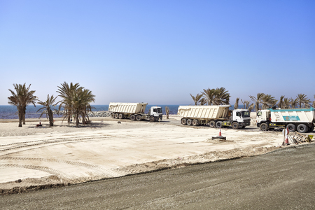 Dubai, United Arab Emirates - May 03, 2017: Dump trucks on a construction site along the road between Dubai and Sharjah.
