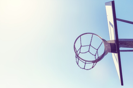 backboard: Basketball hoop with chain net at sunset, color toning applied, space for text.