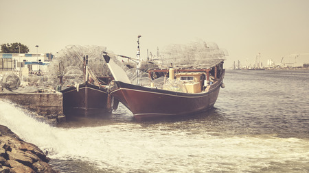 Fishing boats in Ajman harbor, color toning applied, United Arab Emirates.