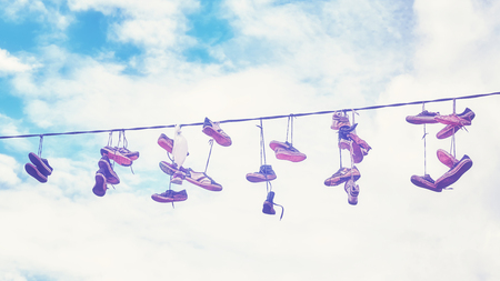 Vintage stylized picture of old dirty shoes hanging on wire.