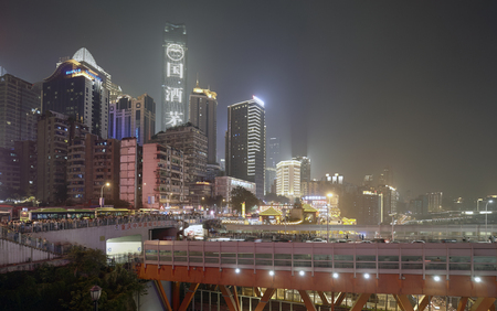 Chongqing, China - October 2, 2017: Crowded Chongqing city downtown shrouded in smog at night.