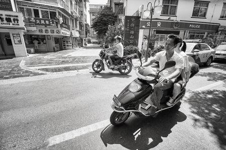Guilin, China - 16 september 2017: Mensen rijden scooters op de straat van Guilin. In sommige steden worden elektrische scooters wettelijk behandeld als fietsen.