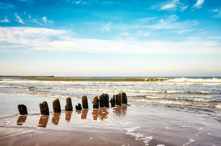 Old wooden groyne on a beach, peaceful natural background.