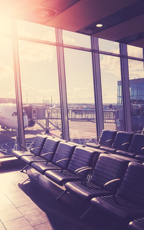 Empty seats in the departure hall at an airport at sunset, color toned travel and transportation concept picture with lens flare effect.