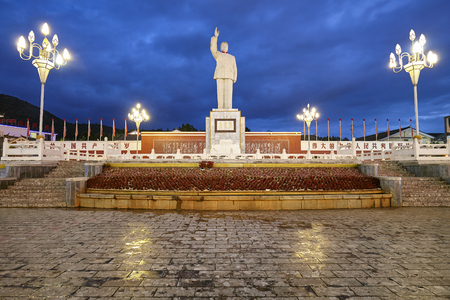 Lijiang, China - September 22, 2017: Mao Tse Tung statue in the Red Sun Square at night. Editorial