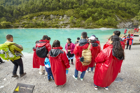 Lijiang, China - September 22, 2017: Tourists listen tour guide at the White Water River in Blue Moon Valley, one of the China top travel destinations.