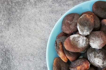 Moldy dried apricots on a plate, space for text. Stock Photo