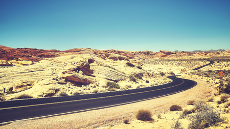 Vintage toned desert road, travel concept, Valley of Fire, Nevada, USA. Stock Photo