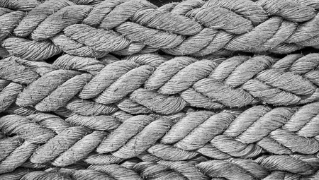 Black and white close up picture ofold frayed boat ropes.