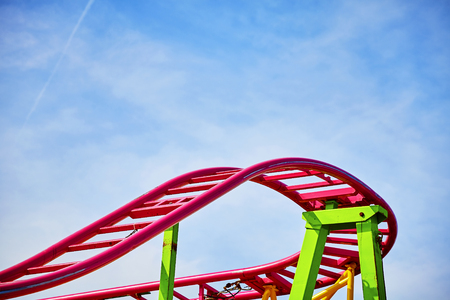 Roller coaster pink tracks in an amusement park, ups and downs concept picture.
