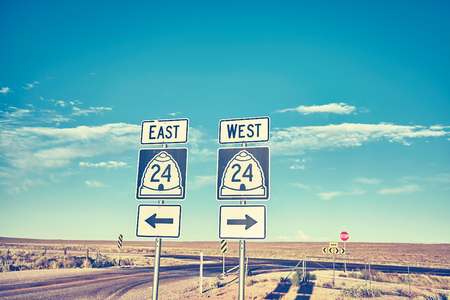 East or West, retro toned photo of road signs at sunset, choice and travel concept.