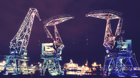 Illuminated old port cranes on a boulevard in Szczecin City at night, color toning applied, Poland. Stock fotó - 106367371