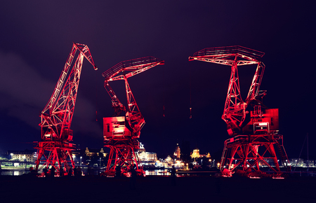 Illuminated old port cranes on a boulevard in Szczecin City at night, color toning applied, Poland.