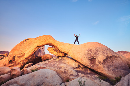 Unique rock formations at Joshua Tree National Park with female climber at sunset, California, USA.
