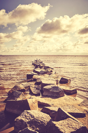 Vintage toned picture of a rocky breakwater at sunset. Stok Fotoğraf