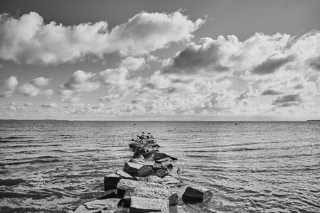 Black and white picture of a rocky breakwater.