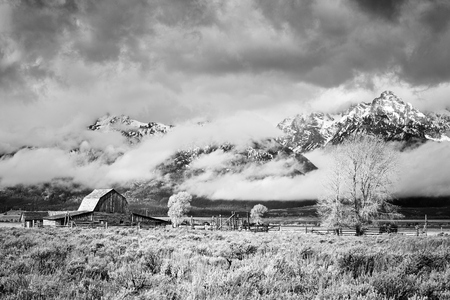 Teton Mountain Range with Moulton Barn in clouds, Grand Teton National Park, Wyoming, USA.