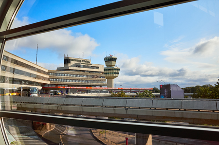 Berlin, Germany - August 15, 2018: Tegel Airport main building and traffic control tower seen through a window in the morning.