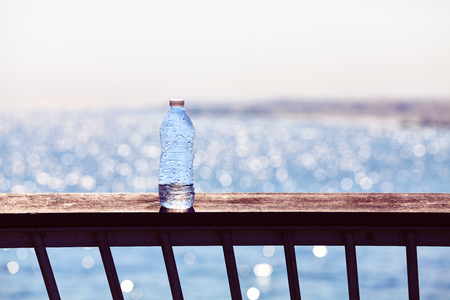Empty plastic bottle left on a pier balustrade at sunset, selective focus, color toning applied.