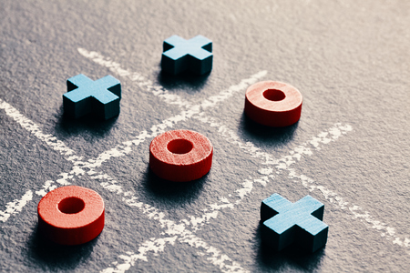 Close up picture of tic tac toe game (noughts and crosses) on dark background, selective focus, color toning applied. Banco de Imagens