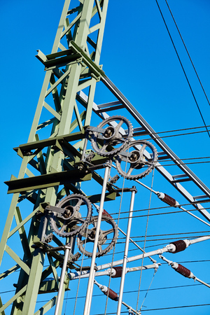 Overhead train electric traction system against the blue sky. Stock Photo