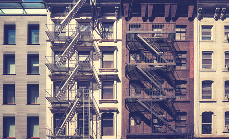 Old buildings with fire escapes, vintage toning applied, New York City, USA. Stock Photo