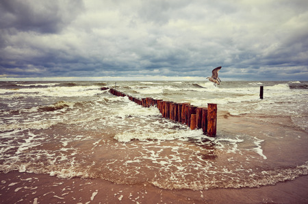 Vintage toned seascape with an old wooden breakwater.
