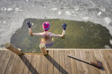 Fit woman performs ice swim in the ice hole. Holding hands above the water protects from fast hypothermia. 写真素材