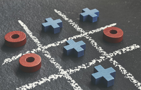 Close up picture of tic tac toe game (noughts and crosses) on dark background, selective focus.