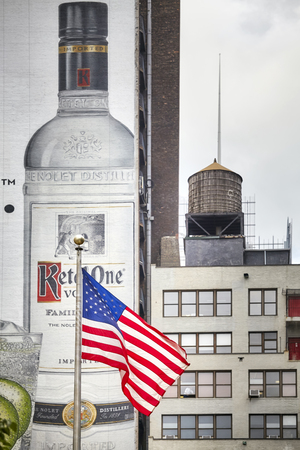 New York, USA - June 28, 2018: Flag of the United States of America with Ketel One Vodka banner and water tank in background in downtown Manhattan.