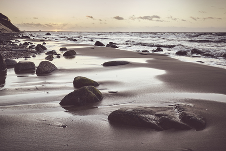 Scenic beach with a stones at sunset, selective focus, color toning applied. Stock fotó