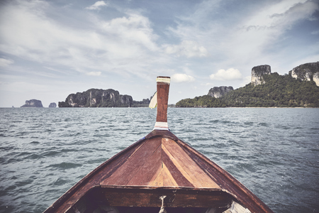 Wooden boat bow with islands in background, retro color toned picture, Thailand.