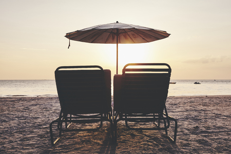 Empty beach chairs and umbrella silhouettes at sunset, color toned picture.