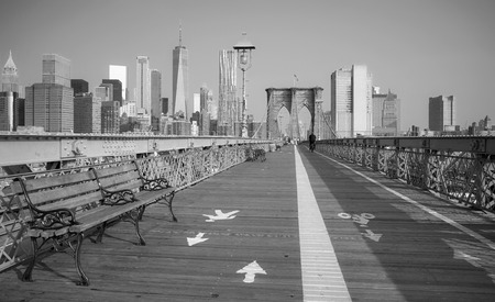 Black and white picture of Brooklyn Bridge with Manhattan skyline, NYC.