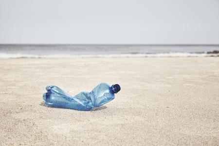 Botella de plástico vacía en una playa, enfoque selectivo, tonificación de color aplicada.