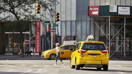 New York, USA - July 01, 2018: Female athlete runs across pedestrian crossing at Columbus Circle on a summer morning. Publikacyjne