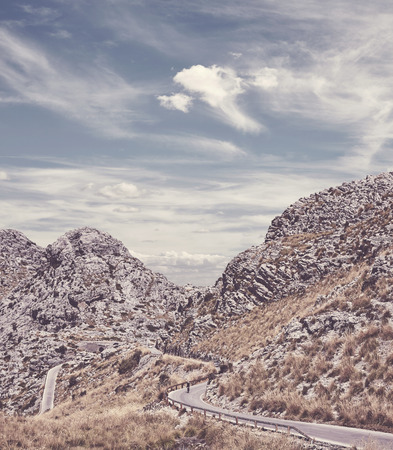 Retro toned picture of a scenic winding mountain road, Mallorca, Spain.