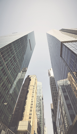 Looking up at Manhattan skyscrapers, retro color toned picture, New York City, USA.