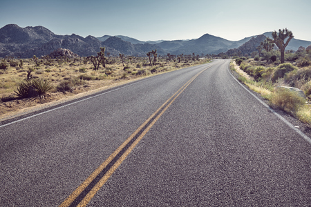 Vintage stylized picture of a desert road at sunset, front focus on asphalt, California, USA.