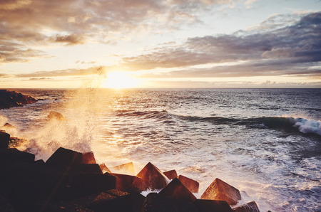 Scenic sunset with waves crashing on rocks, color toning applied, Puerto de la Cruz, Tenerife, Spain.