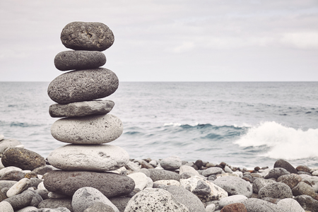 Color toned picture of a stone stack on a beach, balance and harmony concept, selective focus.