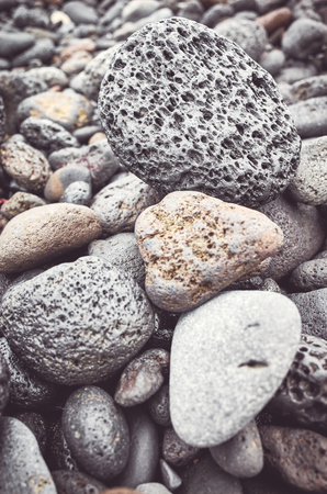 Natural background made of volcanic rocks and pebbles, selective focus, color toning applied.