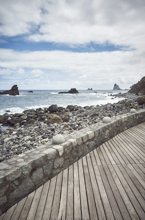 Wooden boardwalk by the Roque de Las Bodegas Beach, retro color toning applied, Tenerife, Spain. Stock Photo