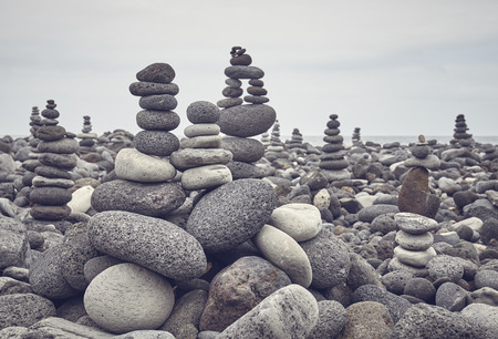 Stone stacks on a beach, color toning applied, selective focus.