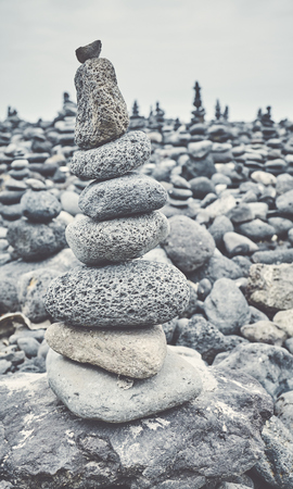 Color toned picture of a stone stack on a beach, selective focus.