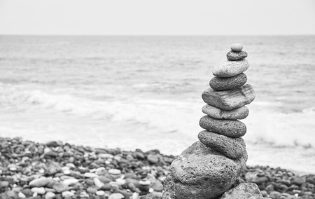 Black and white picture of a stone stack on a beach, selective focus.