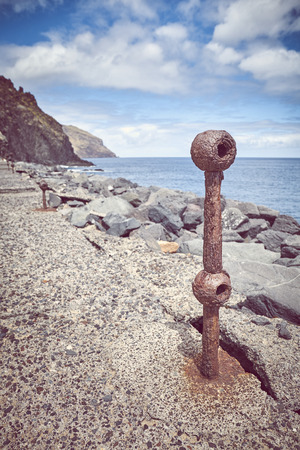 Old rusted piece of guard rail on a quay at Beach De Las Teresitas in San Andres, selective focus, color toning applied, Tenerife, Spain.