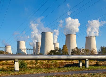 Elektriciteitscentrale rokende schoorsteen bij zonsondergang, milieuvervuiling concept. Stockfoto