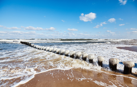Beach with an icy breakwater on a sunny winter day.
