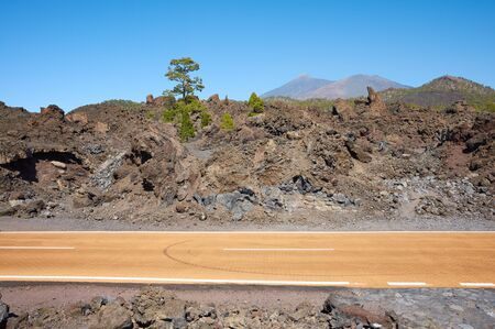 Road with Teide volcano in distance, Teide National Park, Tenerife, Spain. Stockfoto